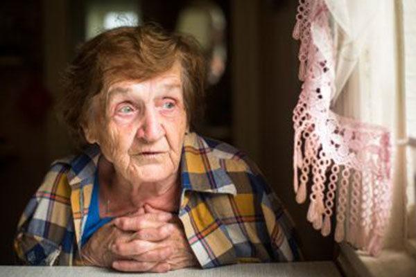 Ältere Dame sieht aus dem Fenster