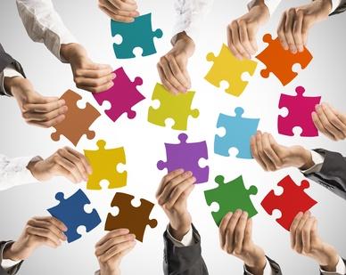 Hände halten Puzzleteile in der Hand
